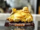 Phật di lạc vàng bóng tay cầm nén vàng nằm trên túi tài lộc vàng đế gỗ LN190